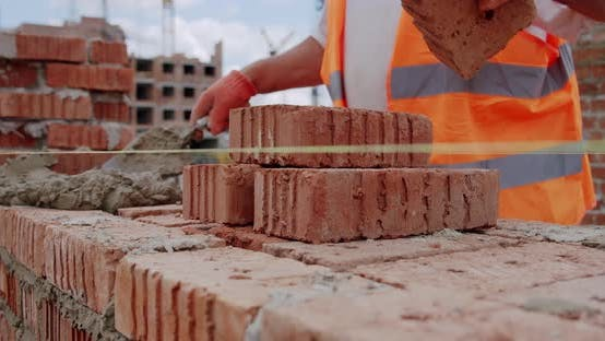 Thumbnail for Male Worker Lays Brick Into Wall with Cement Using Trowel. Close Up V2