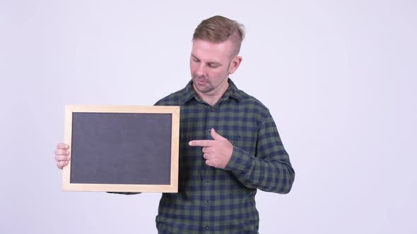 Cover Image for Portrait of Happy Blonde Hipster Man Holding Blackboard and Giving Thumbs Up