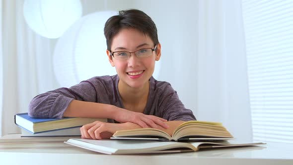 Thumbnail for Mixed race Asian woman with a pile of books