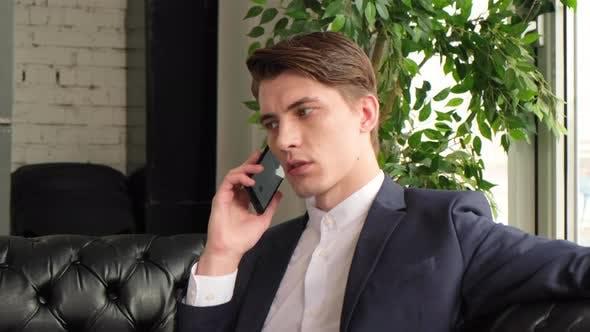 Thumbnail for Geschäftsmann, der Laptop benutzt, der mit Handy spricht, sitzt am Schreibtisch. Glücklich selbstbewusster männlicher