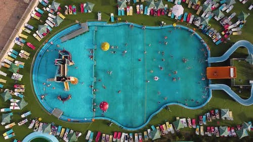 Aerial top view of people swimming in the large open-air pool