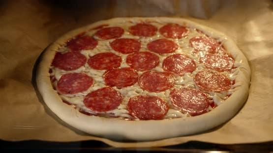 Timelapse Pizza Peperoni wird im Ofen auf Papier gebacken.
