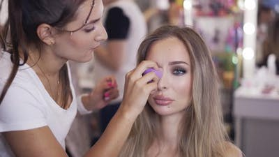 Makeup Artist Doing Makeup Apply Foundation with Blender