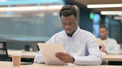African Businessman Reading Documents in Office