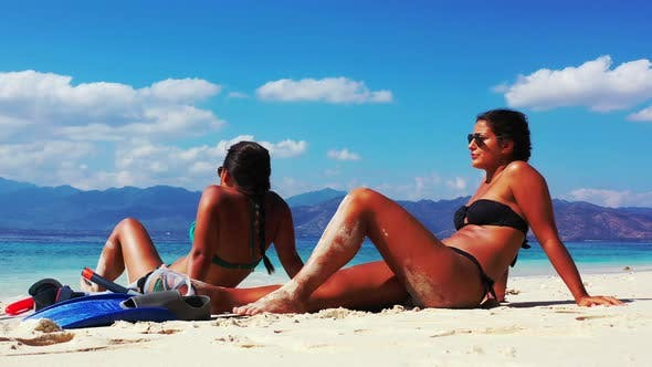 Thumbnail for Beautiful beauty models relaxing in the sun at the beach on clean white sand and blue background 4K