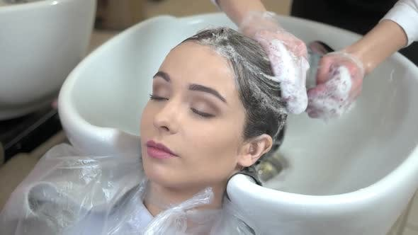 Beautician Washing Head of Client