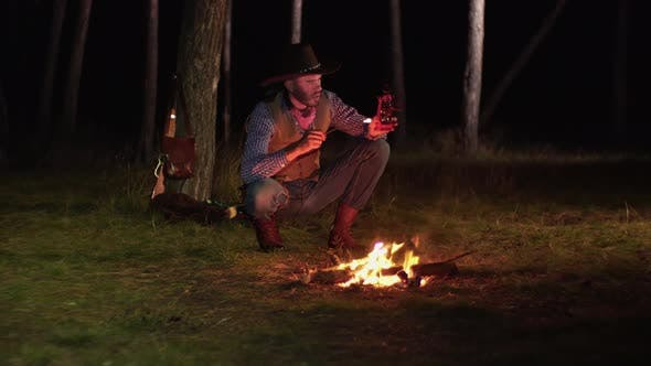 Thumbnail for Cowboy Lights a Kerosene Lamp in the Forest at Night