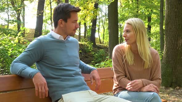Thumbnail for A Man and a Woman (Both Young and Attractive) Sit on a Bench and Talk in a Park on a Sunny Day