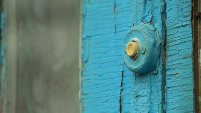 Woman Pressing the Doorbell Button on the Old Blue Door