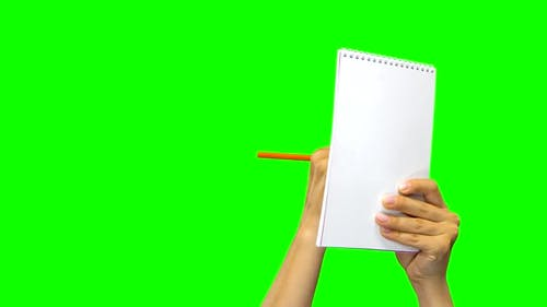 Hands Writing Down Something in Notebook