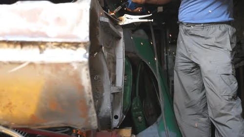 Male Hand of Repairman or Mechanic Worker Welds Metal Parts of Old Car with Welding Machine in