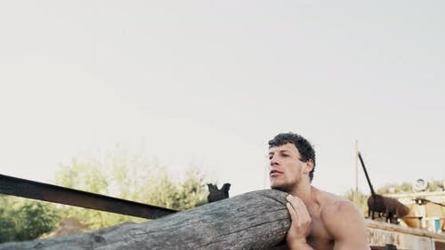 A Young Athlete Trains His Shoulders with a Ponderous Wooden Beam on the Open Air. The Concept of