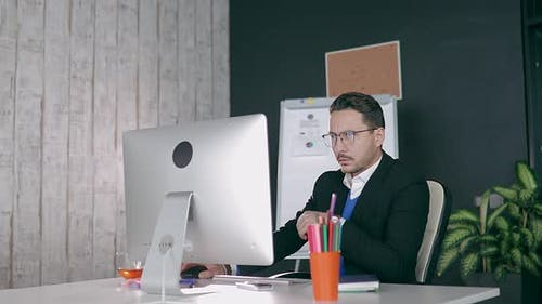 Businessman in Glasses Sits at Computer in Office