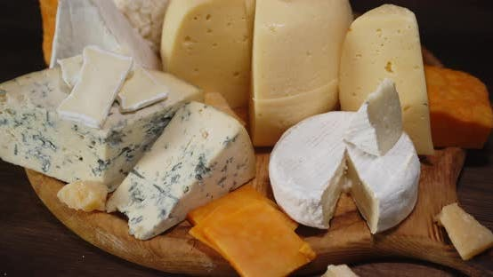 Pieces of Different Types Cheese on Board Slowly Rotate.