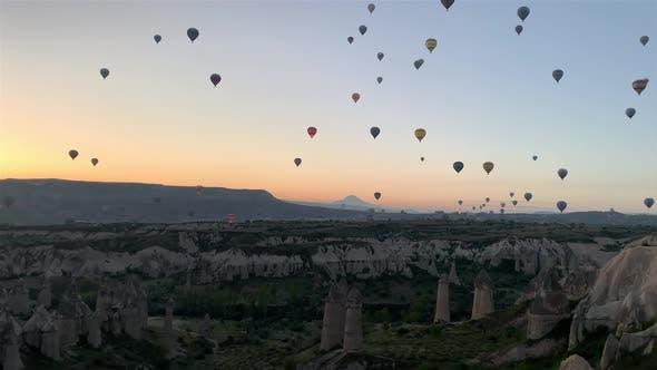Hot-air balloons flying over the mountain landsape of Cappadocia, Turkey.