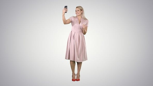 Mature woman wearing light pink dress making selfie on