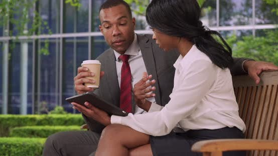 Thumbnail for Two African-American business professionals discuss business plan on tablet