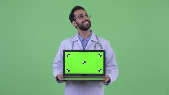 Thumbnail for Happy Young Bearded Persian Man Doctor Thinking While Showing Laptop