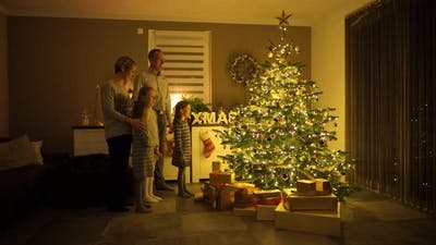 Family Singing in Front of Christmas Tree