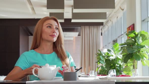 Thumbnail for Gorgeous Happy Woman Pouring Tea in Her Cup, Enjoying Breakfast at Restaurant