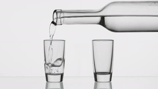 Thumbnail for Pouring Up Two Shot of Vodka From a Bottle Into Glass. White Background
