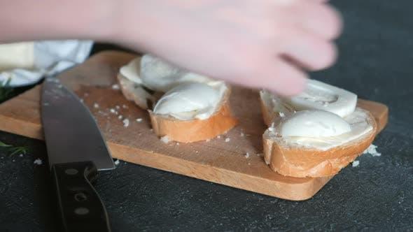 Thumbnail for Handgesalzene Sandwiches mit Brot, Butter und Eiern auf Holzbrett