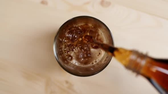 Thumbnail for Top View of Cola Sparkling Drink Pouring in a Glass with Ice Cubes on Light Brown Wooden Table