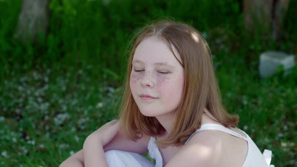 Porträt Sommersprossen Mädchen Teenager sitzt auf grünem Gras im Sommerpark. Gesicht Schöne Teen Mädchen mit