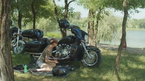 Thumbnail for Stylish Woman Biker Repairing Motorcycle in Park