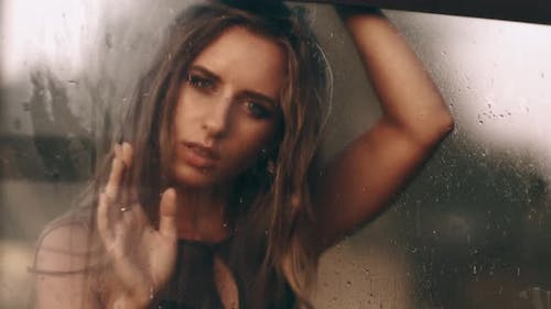 Fashion and Beauty. Window with Water Drops Before Closed Girl with Makeup. Rain Drops on Window