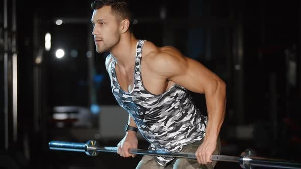 Cover Image for Attractive Sportsman Trains Hands and Shoulders With Barbell Weight
