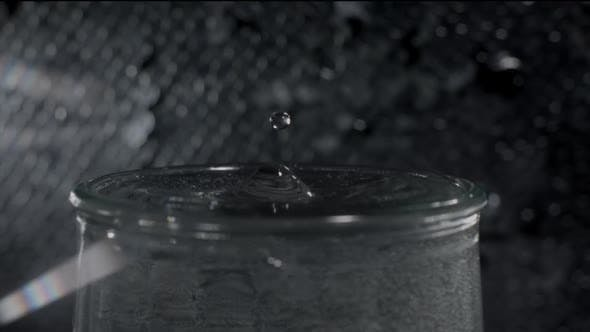 Focused Shot of Full Glass of Water and Droplet Falling