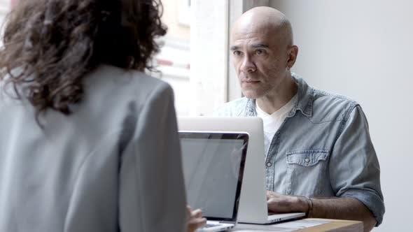 Thumbnail for Zwei selbstbewusste Menschen sitzen am Tisch und nutzen Laptops