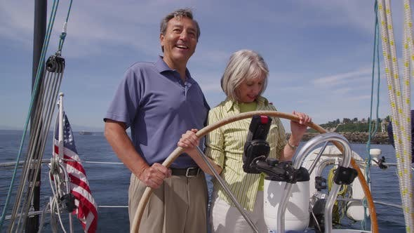 Senior couple behind the wheel of sailboat together. Shot on RED EPIC for high quality 4K, UHD, Ultr