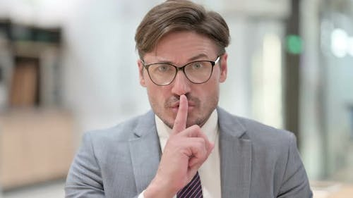 Silence Please, Businessman Putting Finger on Lips