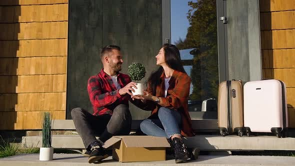 Thumbnail for Lovely Modern Young Man and Woman Which Sitting on the Steps, Holding in their Hands Green Flower