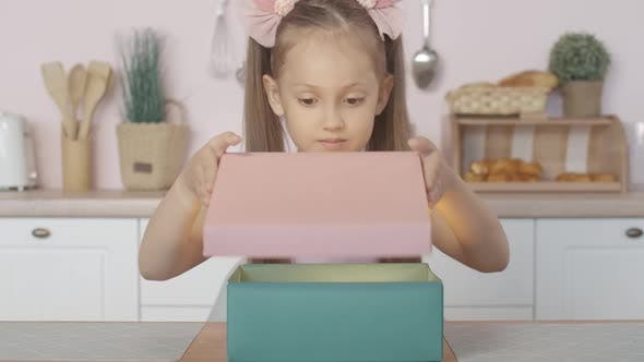 Portrait of Excited Little Girl Opening Gift Box with Surprised Facial Expression, Pretty Brunette