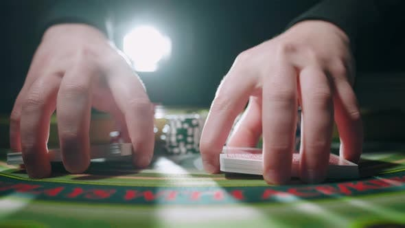 Close Up of Dealer Man Hands Mixing the Poker Cards