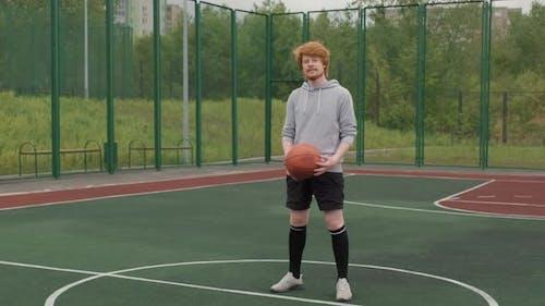 Mann mit Basketball, der draußen nach Kamera lächelt