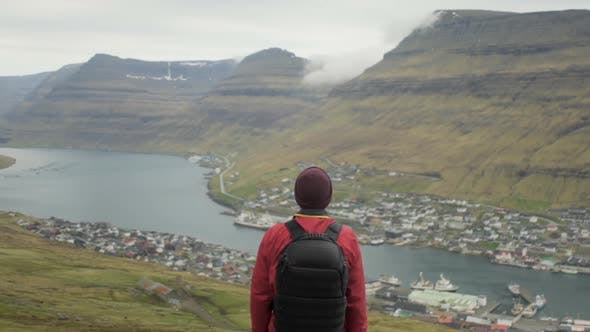 Hiker Standing With Town Below And Mountain Ahead
