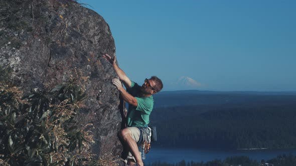 Thumbnail for Man Rock Climbing With Mt Rainier Background