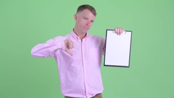 Thumbnail for Portrait of Stressed Businessman Showing Clipboard and Giving Thumbs Down