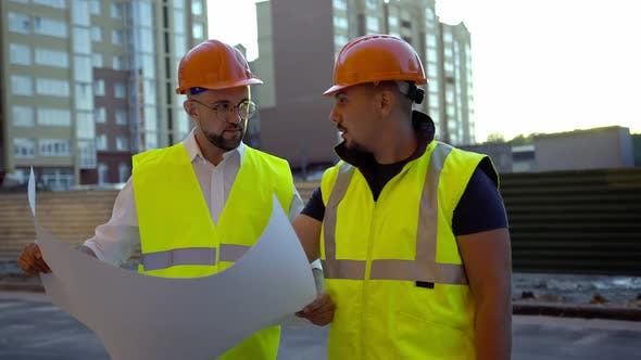 Discussion of Two Young Workers in Helmets