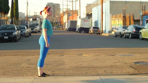 Thumbnail for A young woman doing sprints in the streets of an urban environment.