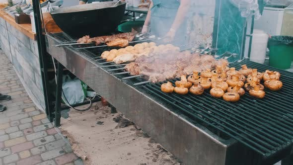 Shish Kebab and Mushrooms on Skewers Cooked on Barbecue at Street Food Festival