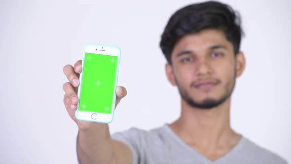 Cover Image for Young Happy Bearded Indian Man Showing Phone