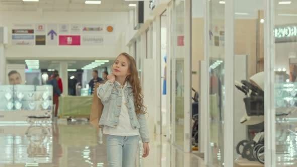 Thumbnail for Cute Little Girl Carrying Shopping Bag, Walking at the Mall