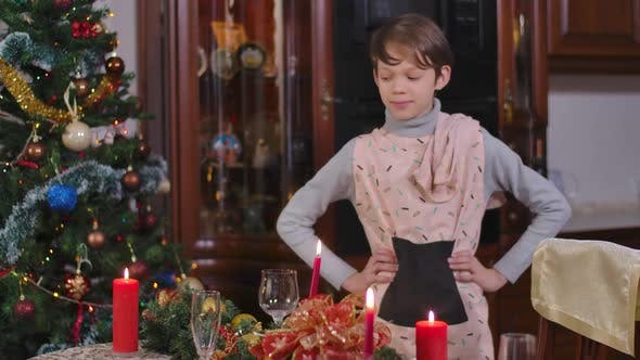 Satisfied Brunette Caucasian Boy Putting Hands on Hips Admiring Decorated Christmas Table