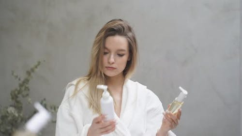 Beautiful Blonde Female Selects Compares Cosmetics Which One Will Be Better