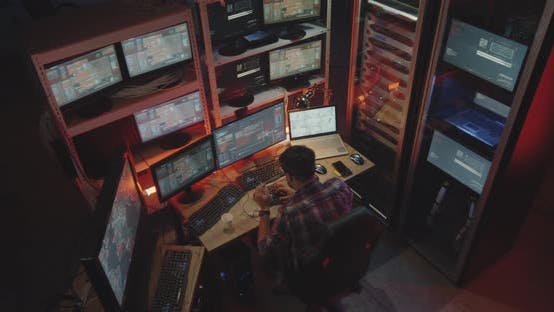 Hacker Using Computer with Multiple Monitors